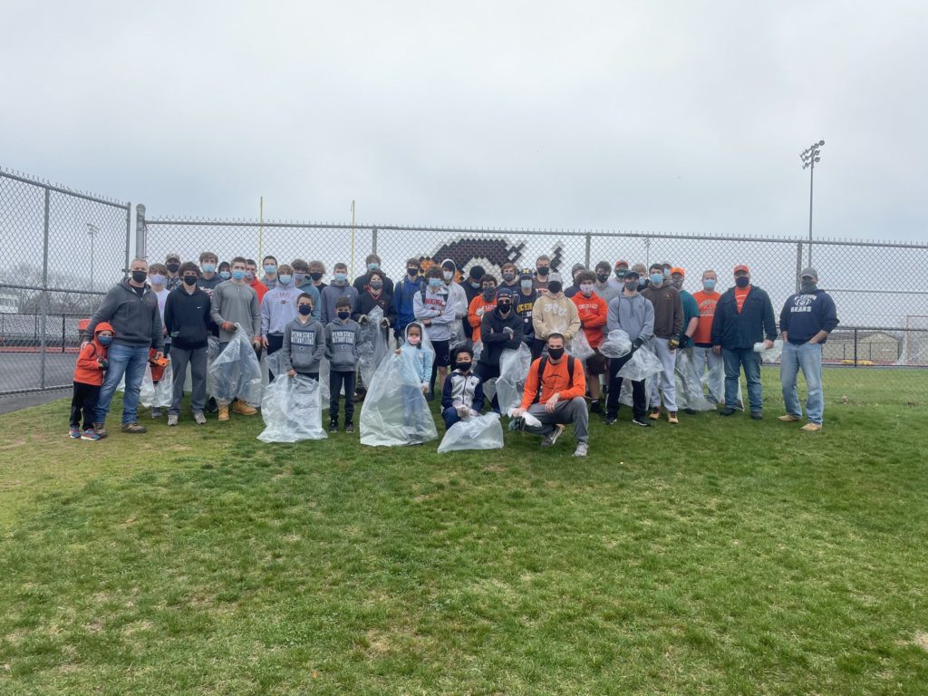 Volunteers from football team help clean up  campus